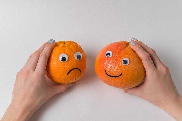 Руки держа апельсин и грейпфрут с смешными сторонами на белизне. пессимист и оптимист