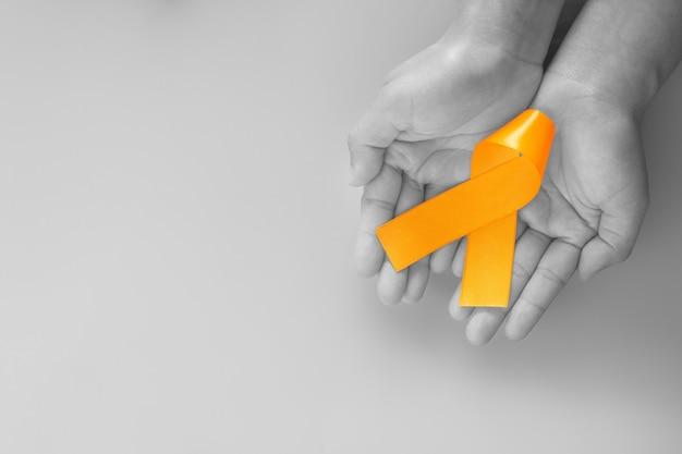 Руки, держащие ленту оранжевого цвета
