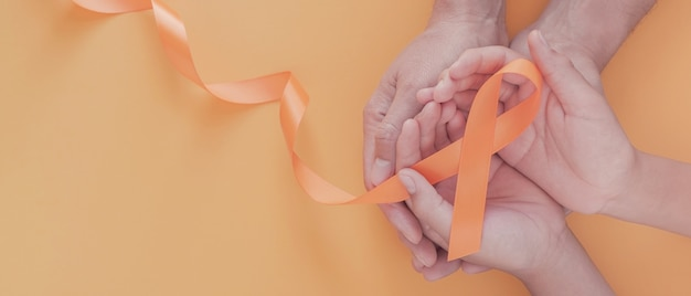 Hands holding orange ribbons