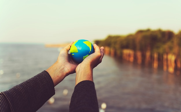 Hands holding out a small globe