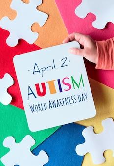 テキストのあるページを持っている手自閉症世界自閉症啓発デー