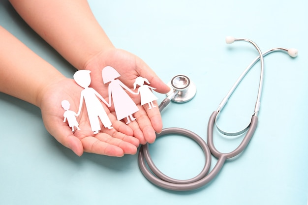 Hands holding paper family cutout with stethoscope on blue.