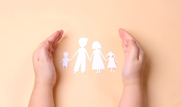 Hands holding paper family cutout