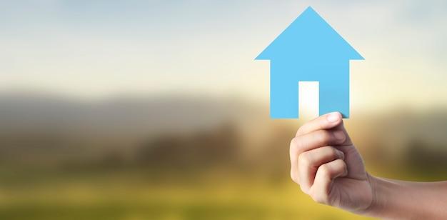 Руки держат бумажный дом, семейный дом и защищают концепцию страхования