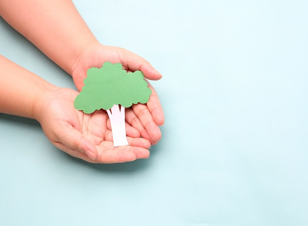 Hands holding paper tree on blue