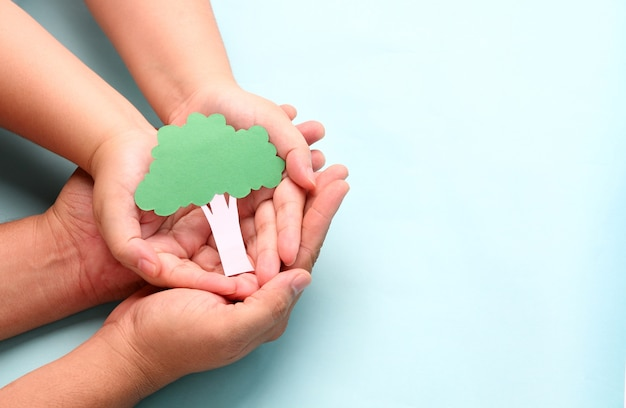 Hands holding paper tree on blue.
