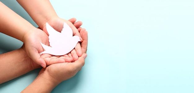 종이 흰 새, 세계 평화의 날 개념을 손에 들고.