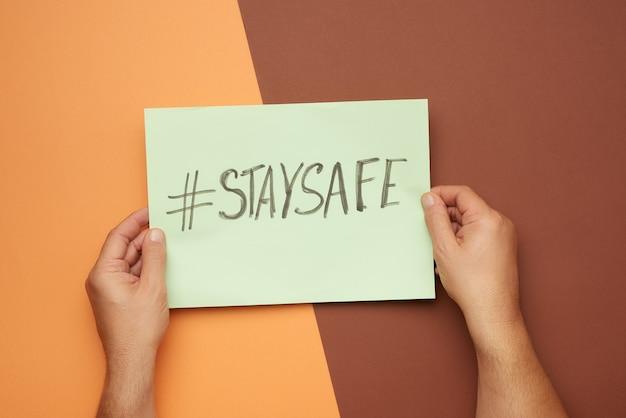 碑文のある紙を持っている手は安全を保ちます