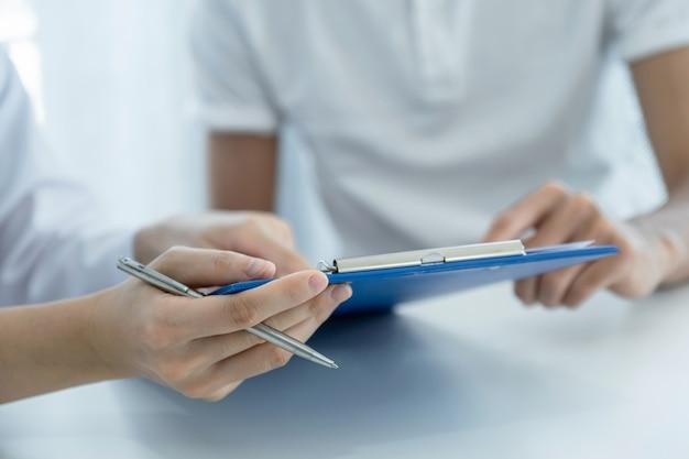 ペンを持った手で、医師は健康診断の結果を報告し、患者に投薬を勧めます。