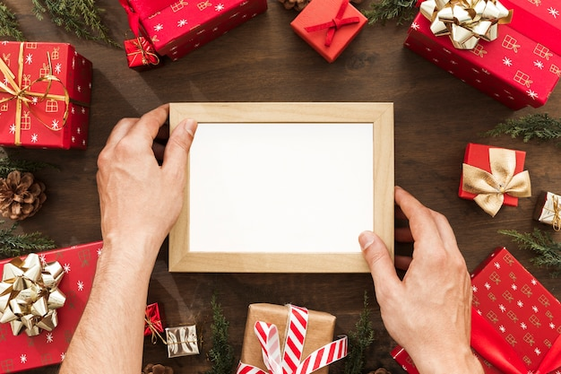 Hands holding photo frame between gift boxes