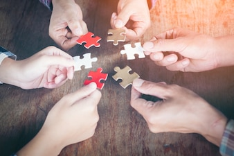 Hands holding piece of blank jigsaw puzzle on black background for teamwork workplace succ