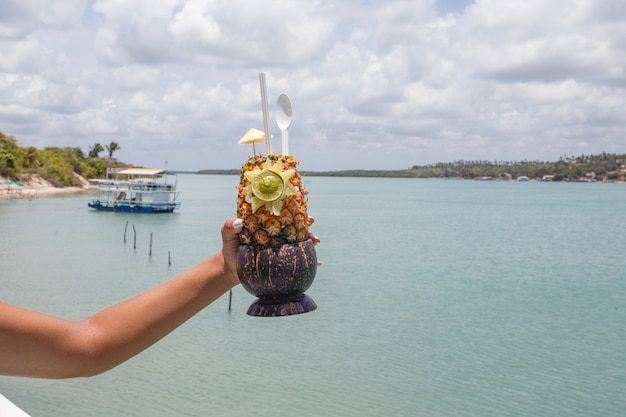 Hands holding pineapple drink with beach background.