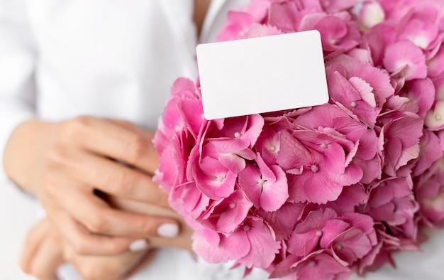 핑크 수국 꽃다발을 들고 손을 닫습니다.