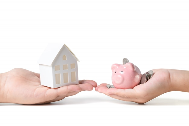 Hands holding pink piggy bank and paper model house isolated