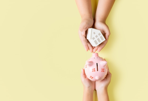 Hands holding pink piggy bank and paper model house