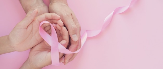 Hands holding pink ribbon, breast cancer awareness, world cancer day concept