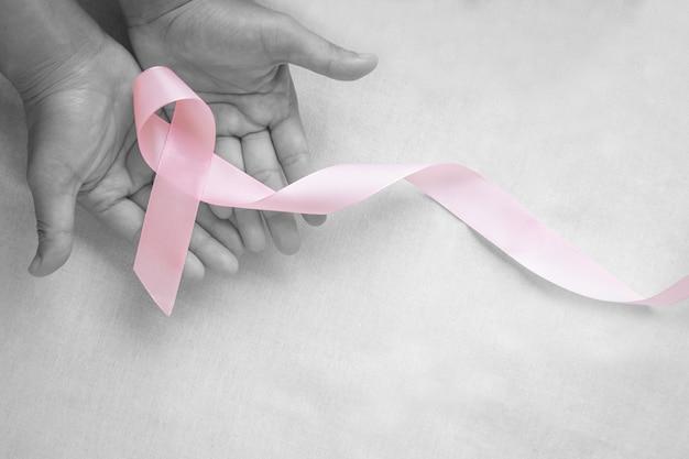 Руки, держащие локон розовой ленты на белой изолированной ткани с копией пространства. осведомленность о раке груди, заболевание мужского рака груди, всемирный день борьбы с раком. концепция здравоохранения или больницы и страхования.