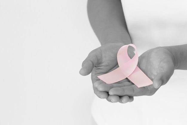 Руки, держащие завиток розовой ленты на белой изолированной ткани с копией пространства