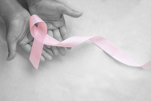 Hands holding pink ribbon curl on white isolated fabric with copy space. breast cancer awareness, male breast cancer disease, world cancer day. healthcare or hospital and insurance concept.