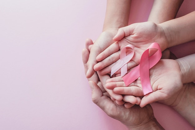 Hands holding pink ribbons on pink background