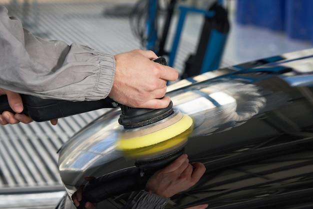 Руки держат полировщик для полировки автомобиля в авто мастерской