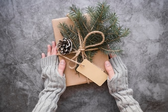Hands holding present box with snags and fir twigs