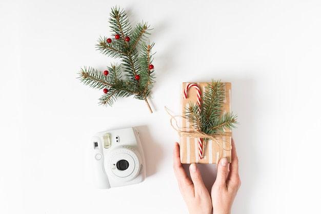 Hands holding present near instant camera