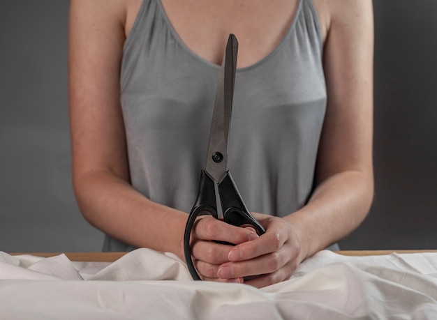 Руки держат профессиональные ножницы швея над натуральной хлопковой тканью