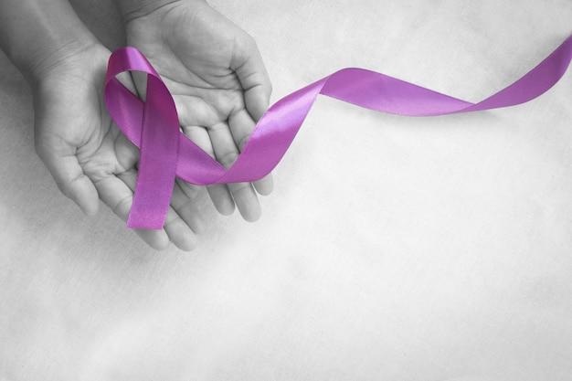 Руки держат фиолетовую или фиолетовую ленту на белой ткани с копией пространства
