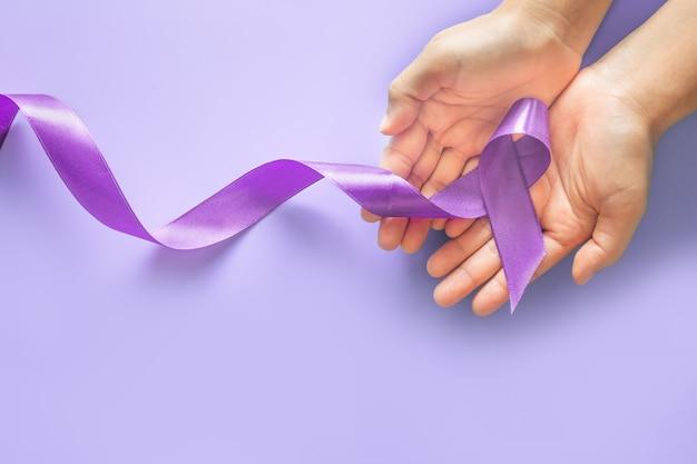 Руки держат фиолетовую ленту на фиолетовом фоне с копией пространства