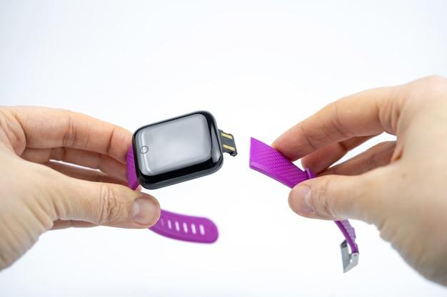 白地に紫のスマートウォッチを持っている手