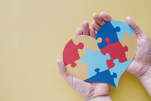 Hands holding puzzle jigsaw heart,  mental health concept, world autism awareness day, pride concept