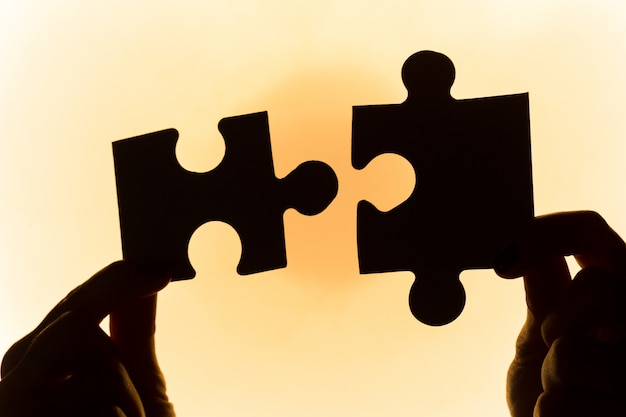 Hands holding puzzle pieces,