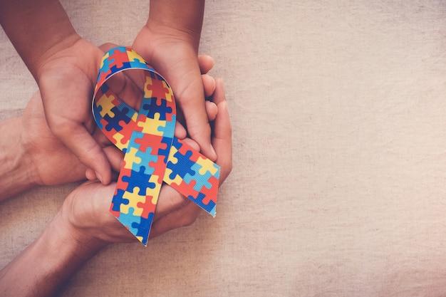 자폐증 인식 퍼즐 리본을 들고 손