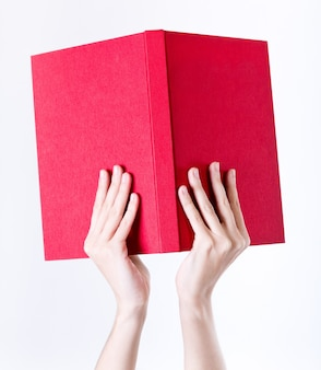 Hands holding red book