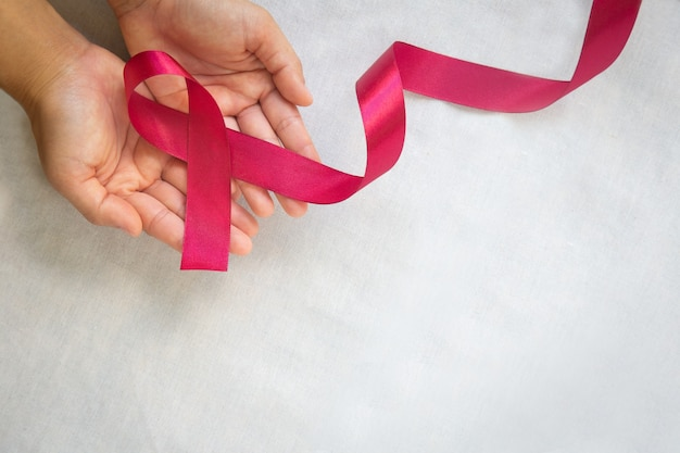 Hands holding red burgundy ribbon bow on white fabric background with copy space, symbol of multiple myeloma or plasma cell cancer.