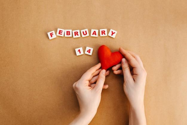 2月14日のテキストの横に赤い手作りのハートを持っている手。