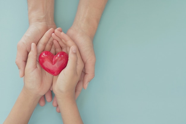 Hands holding red heart, family health insurance  concept, world heart day