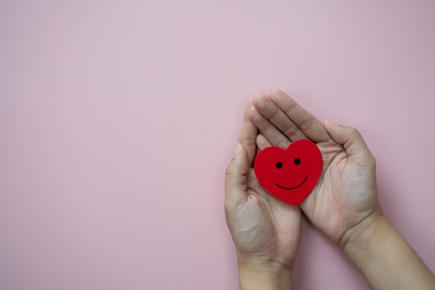 Hands holding red heart with smiley icon on pastel pink background