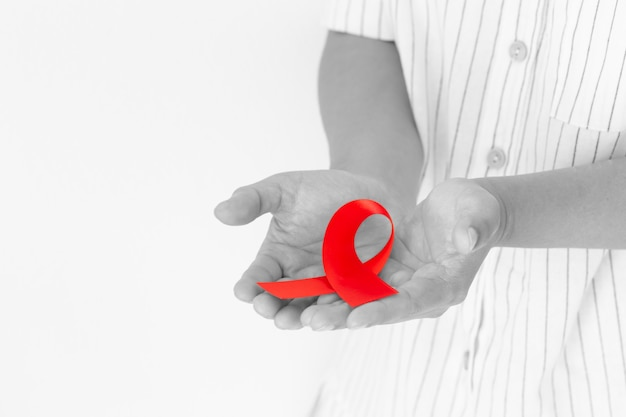 Hands holding red ribbon on white background copy space