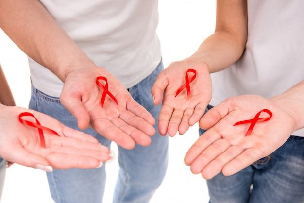 Hands holding red ribbons to rise aids hiv awareness.