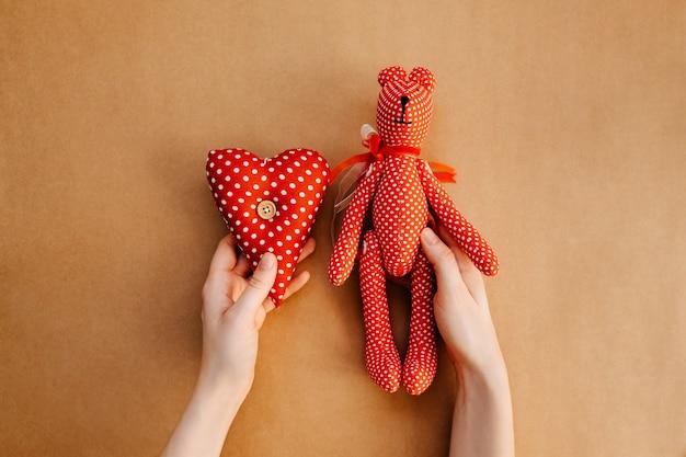 白い水玉のおもちゃのクマとハートで赤を保持している手。