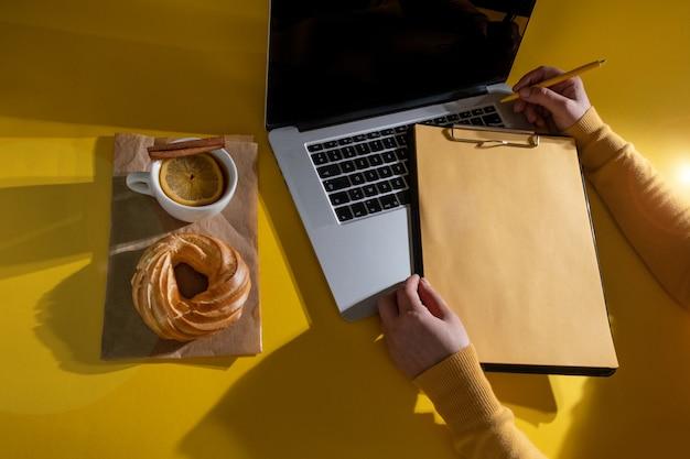 フォーチュナゴールドイエロー色の背景、上面図のラップトップ、ケーキ、お茶の近くに履歴書シートを保持している手。