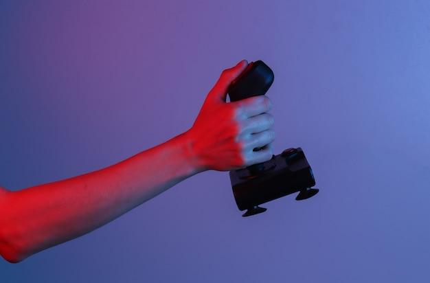 Руки, держащие ретро джойстик в сине-красном неоновом градиентном свете. старая игра. ретро волна 80-х