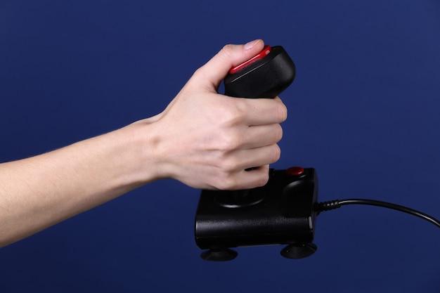 Руки, держащие ретро джойстик на классическом синем фоне. старая игра. ретро волна 80-х