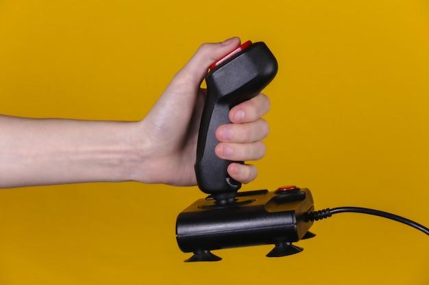 Руки, держащие ретро джойстик на желтом фоне. старая игра. ретро волна 80-х