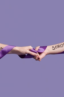 Hands holding a ribbon while covered in empowering words