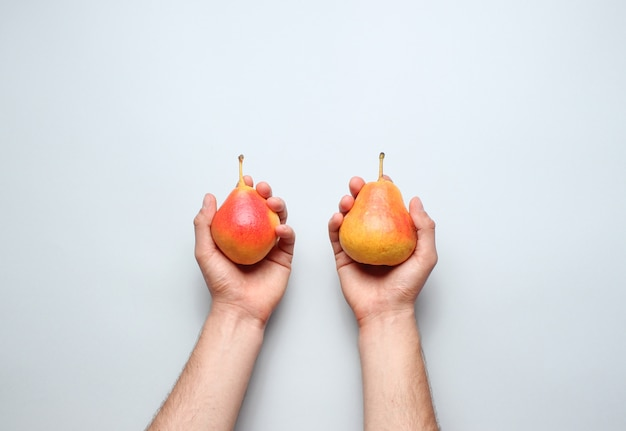 Hands holding ripe autumn pears on a gray table. top view. minimalism