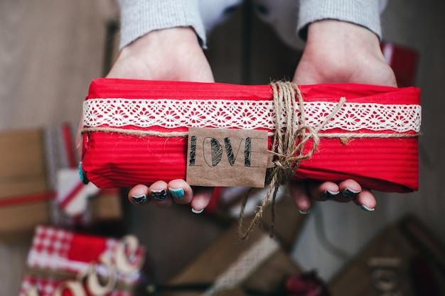 Mani in possesso di un regalo romantico rosso