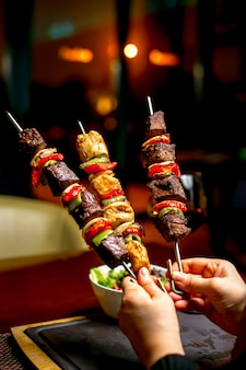 Hands holding shish kebab with colorful bell peppers